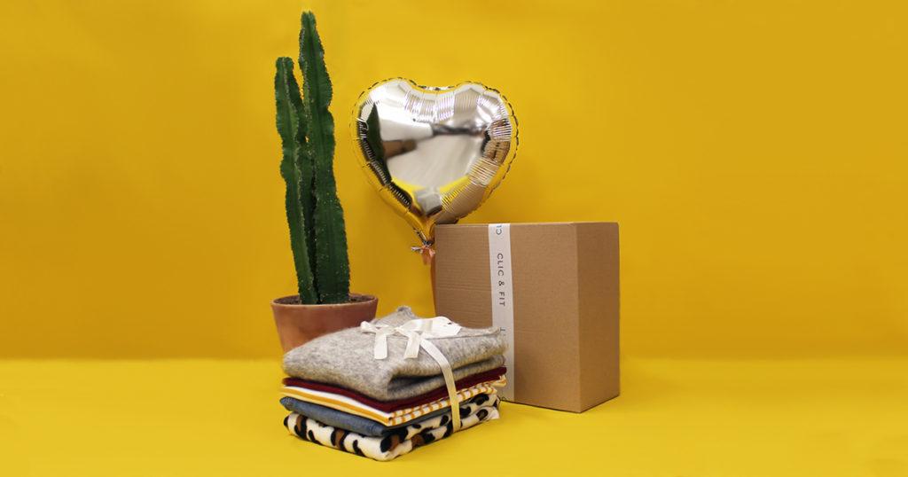 Box Clic and Fit sur un fond coloré avec une pile de vêtements juste devant la box