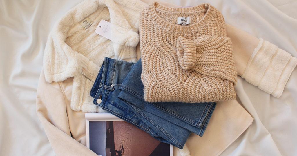 Tenue complète avec un pull en maille esprit cocconing, un manteau chaud et un jean.